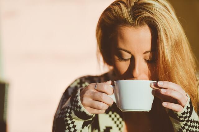 Žena si vychutnává ranní kávu